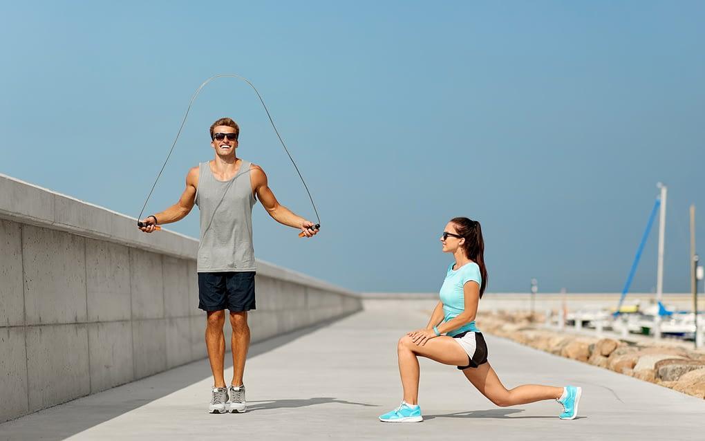 Couple using jump ropes on Australian beach